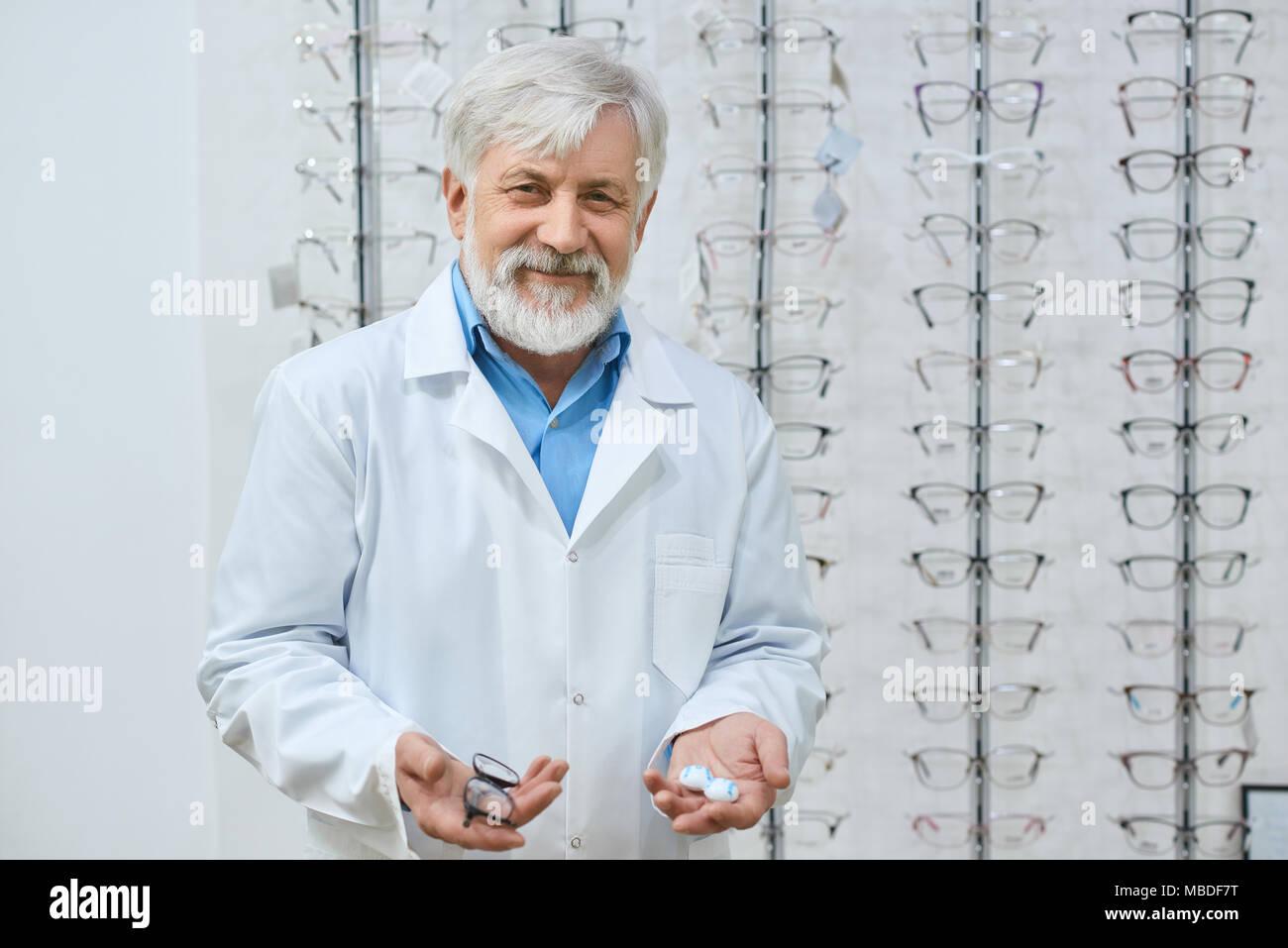 Expirienced oculiste vieux aidant à choisir les lunettes en magasin  ophtalmologique. Oculiste professionnel des compétences de haut niveau. 77807e3e6118