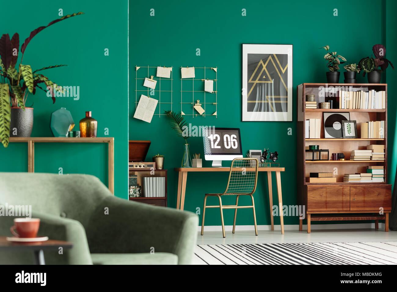 Salon vert intérieur avec des livres sur l'armoire en bois et un bureau pour le travail à distance Photo Stock