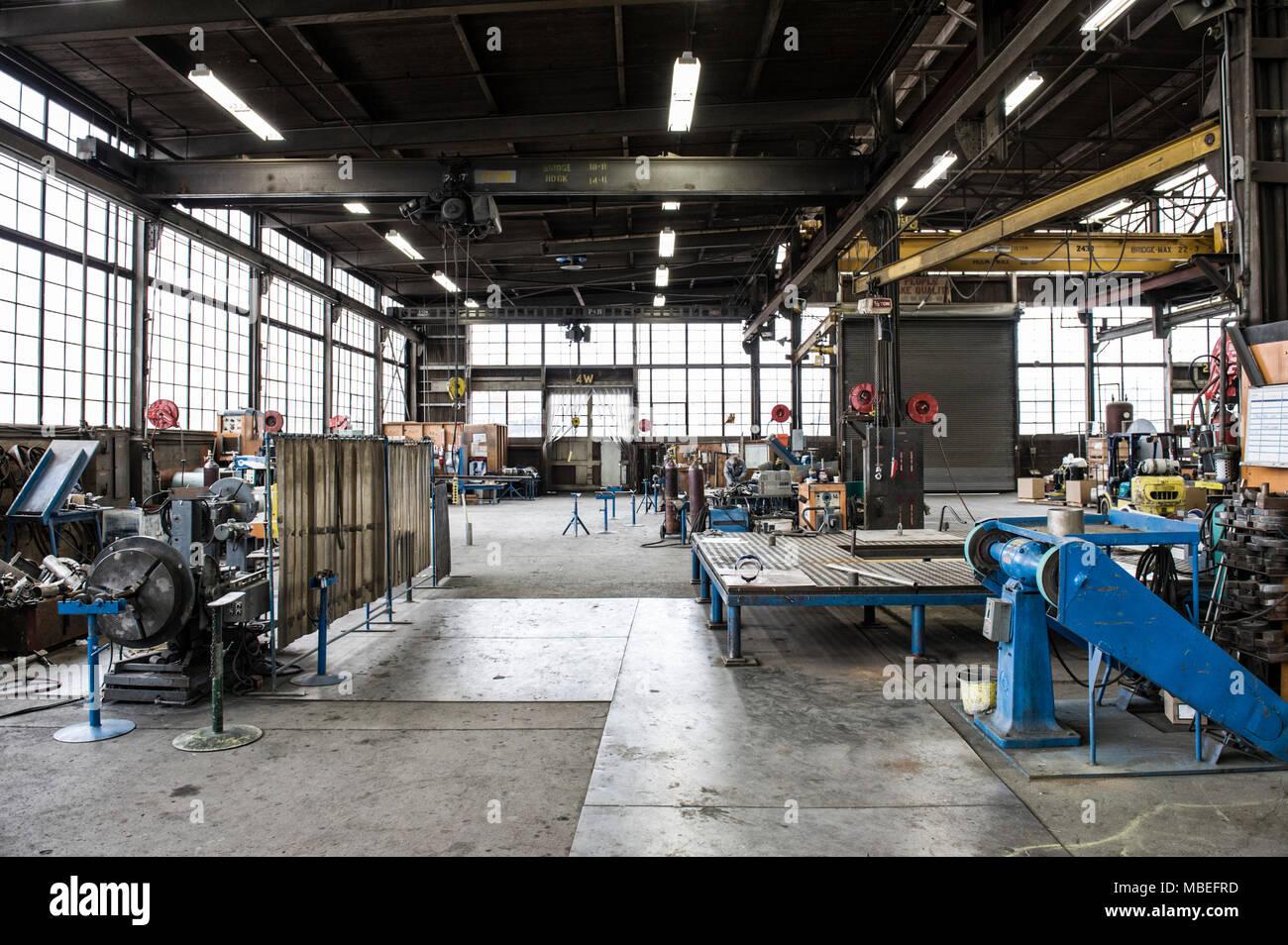 Une usine avec des machines industrielles et des espaces ouverts, presses à métal et des engins de levage et de portiques. La production. Banque D'Images