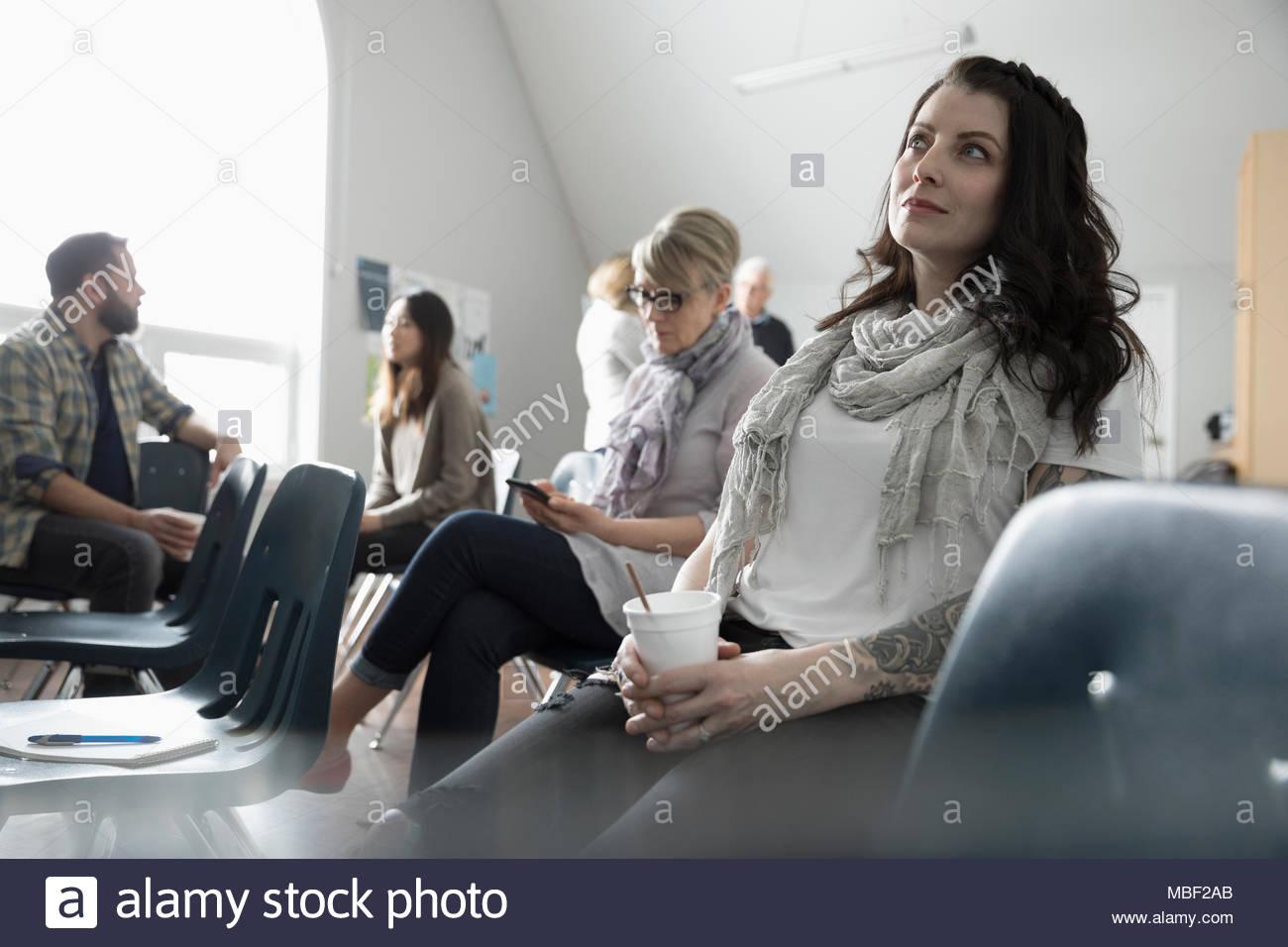Thoughtful woman boire du café et à l'écoute groupe de soutien dans un centre communautaire Photo Stock