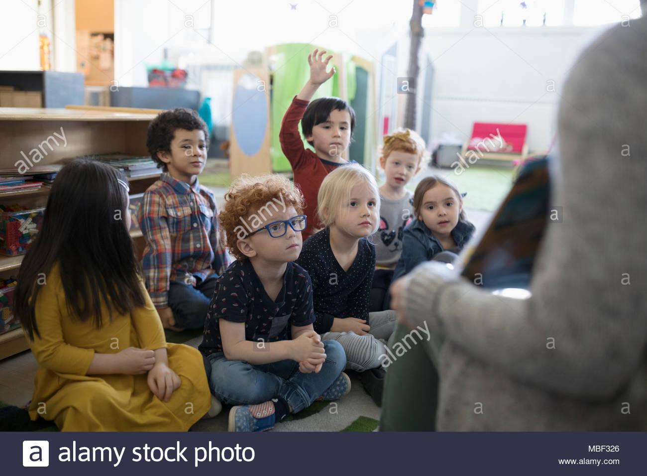 Les élèves de maternelle à l'écoute de l'heure du conte en classe Photo Stock