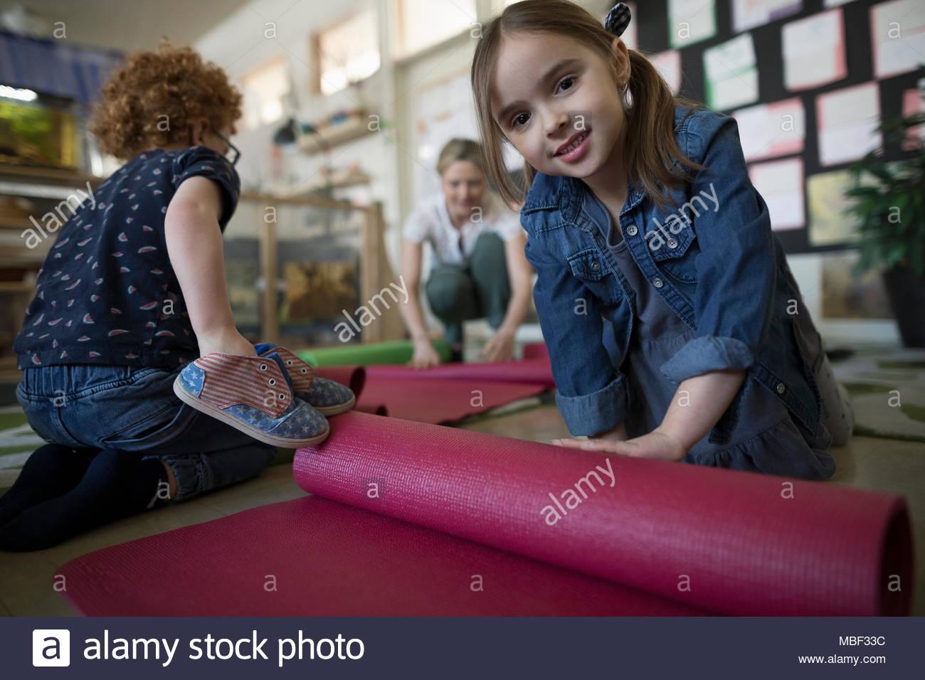 Portrait confiant preschool girl rolling up yoga mat in classroom Photo Stock