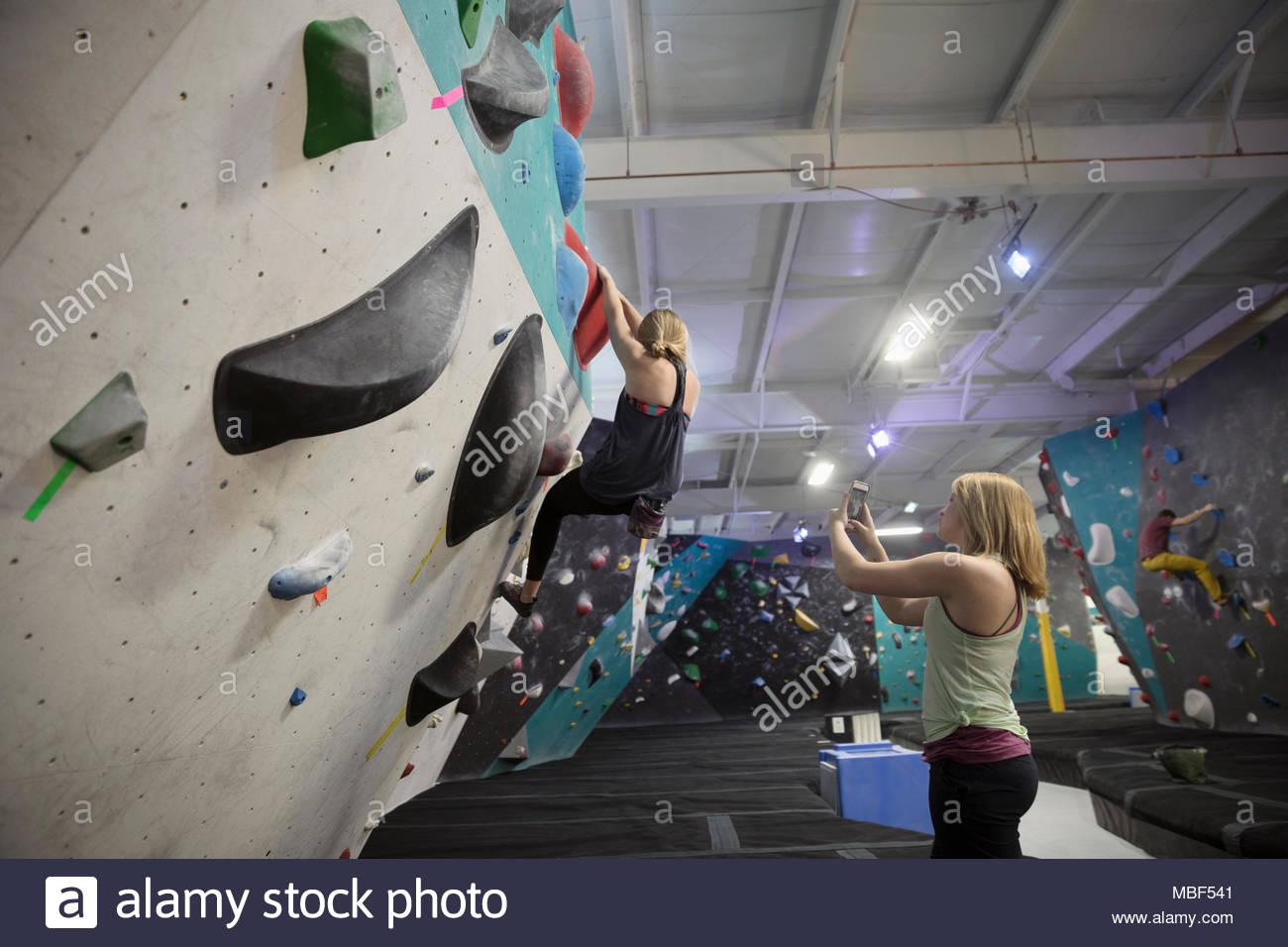 Female rock climber with camera phone filmer partner mur d'escalade à l'escalade Photo Stock