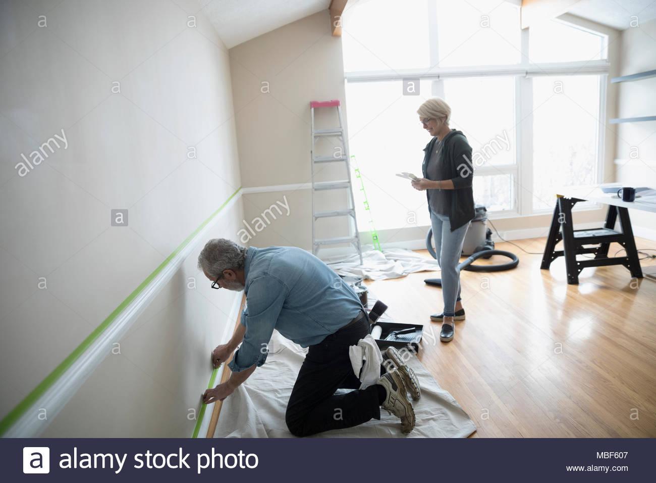 Couple l'enregistrement, la préparation à la peinture décoration de dans la salle de séjour, bricolage Photo Stock