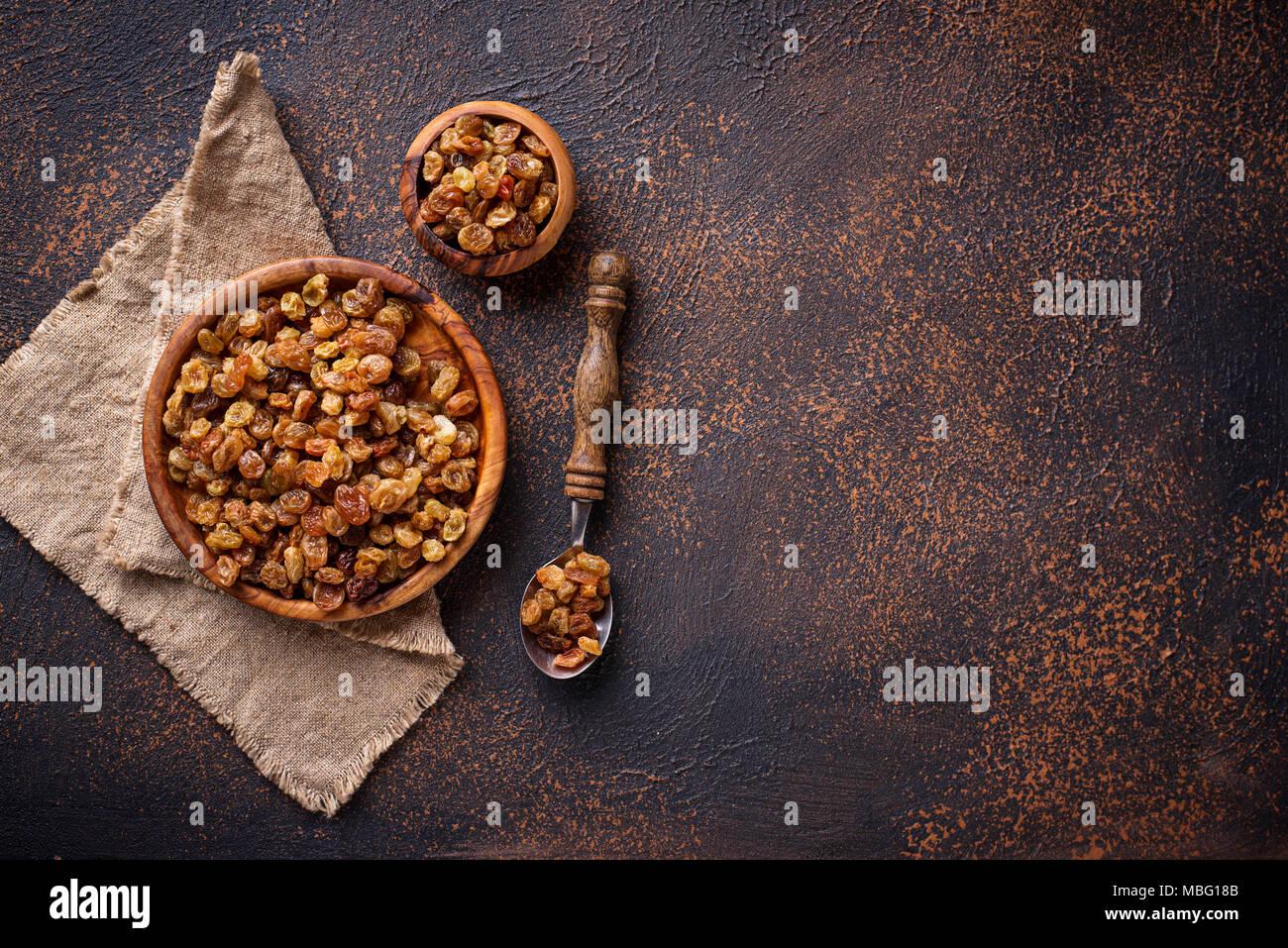 Les raisins secs dans un bol en bois sur fond rouille Banque D'Images