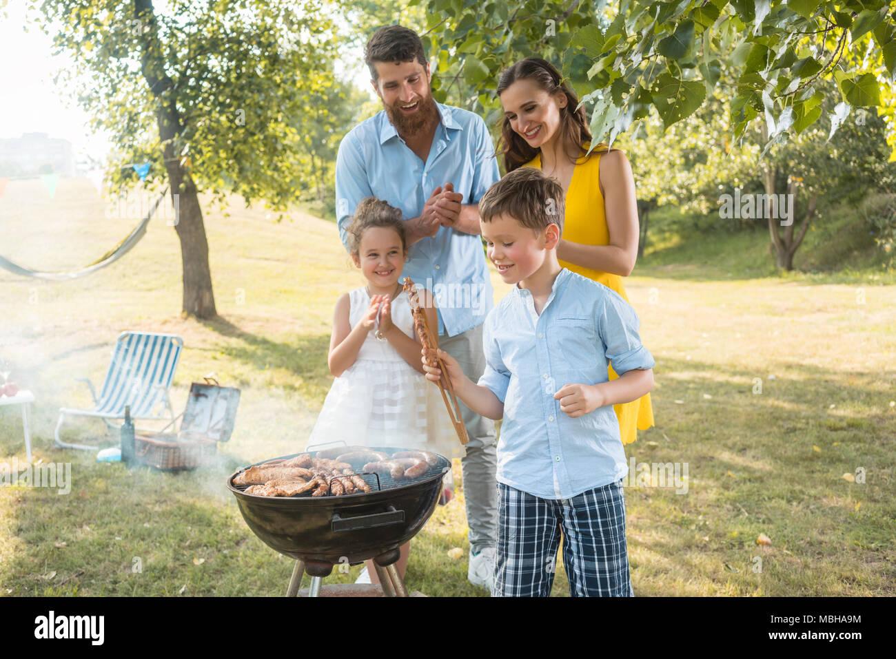 Portrait de famille heureuse avec deux enfants à l'extérieur près du barbecue Photo Stock