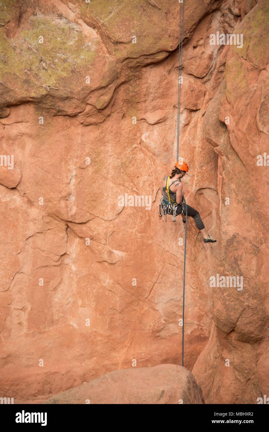 Rock Climber woman rappeling en ordre décroissant vers le bas de falaises de grès sur l'assurage dans le Jardin des Dieux, à Colorado Springs, Colorado, Etats-Unis, le 4 avril 2016 Banque D'Images