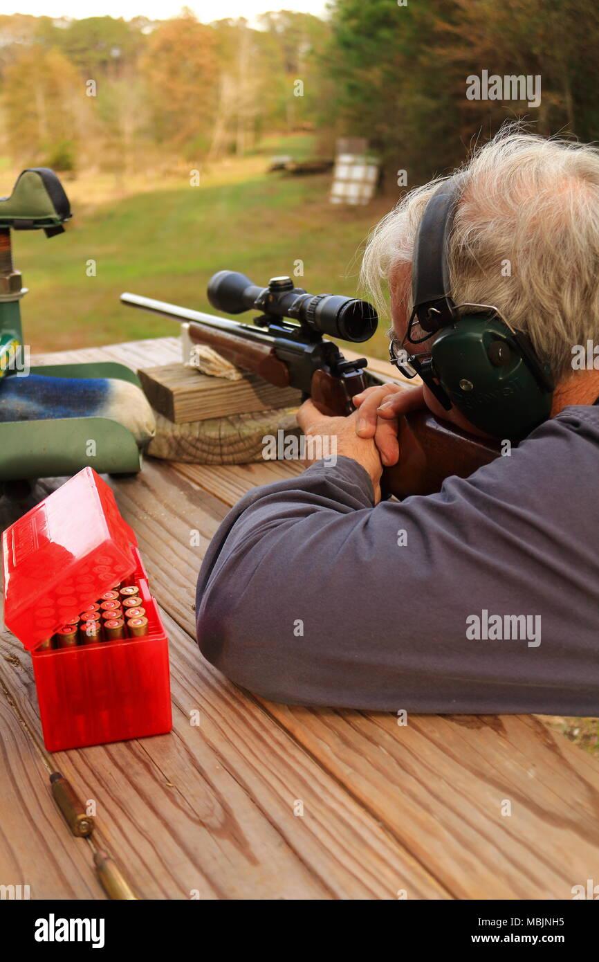 Observation de monsieur plus âgé dans un fusil de chasse à un stand de tir en plein air Photo Stock