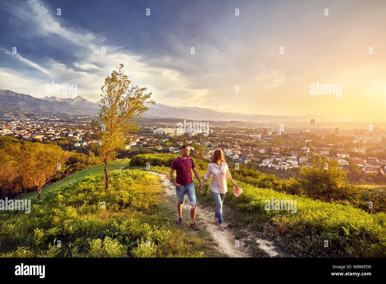 Yong couple dans des vêtements rose balade dans le parc au coucher du soleil vue sur la ville historique. Photo Stock