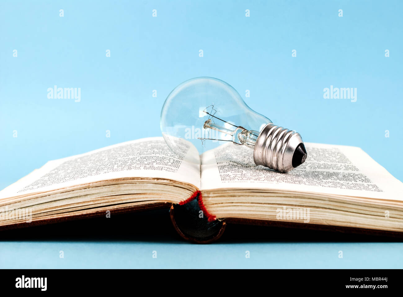 Livre Ouvert Sur L Ampoule Isole Sur Un Fond Bleu Banque D