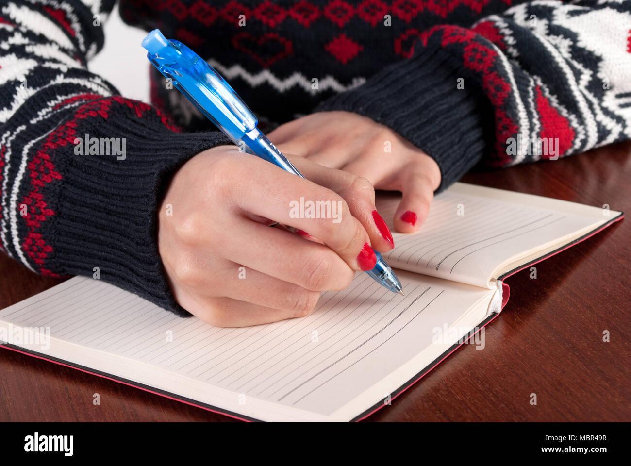 Jeune femme écrit au crayon dans lordinateur portable sur un bureau