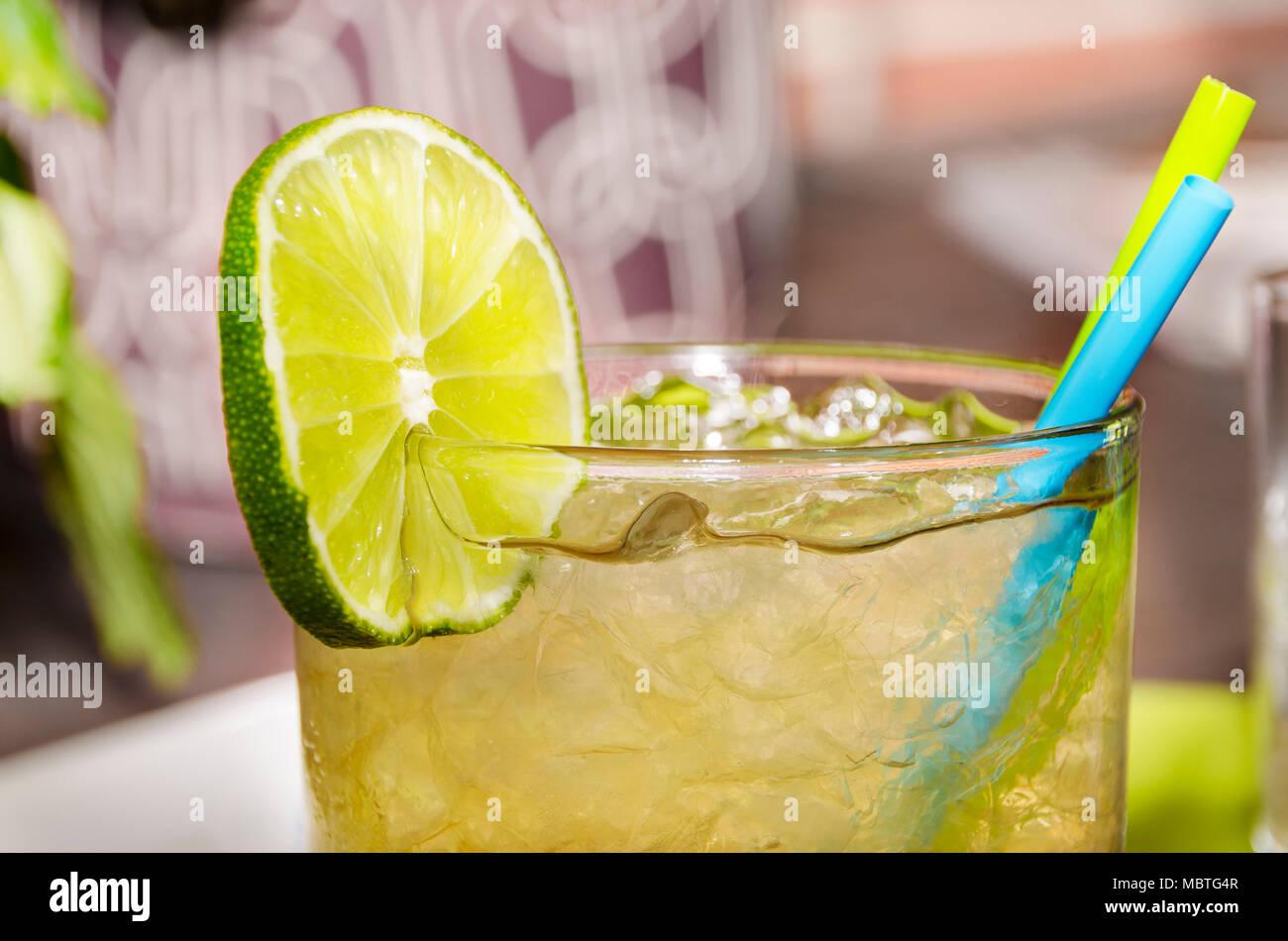 Boisson glacée avec une tranche de lime dans un verre avec deux pailles Photo Stock