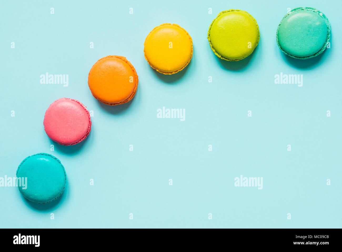 Macarons colorés disposés comme arc-en-ciel sur fond bleu. Banque D'Images