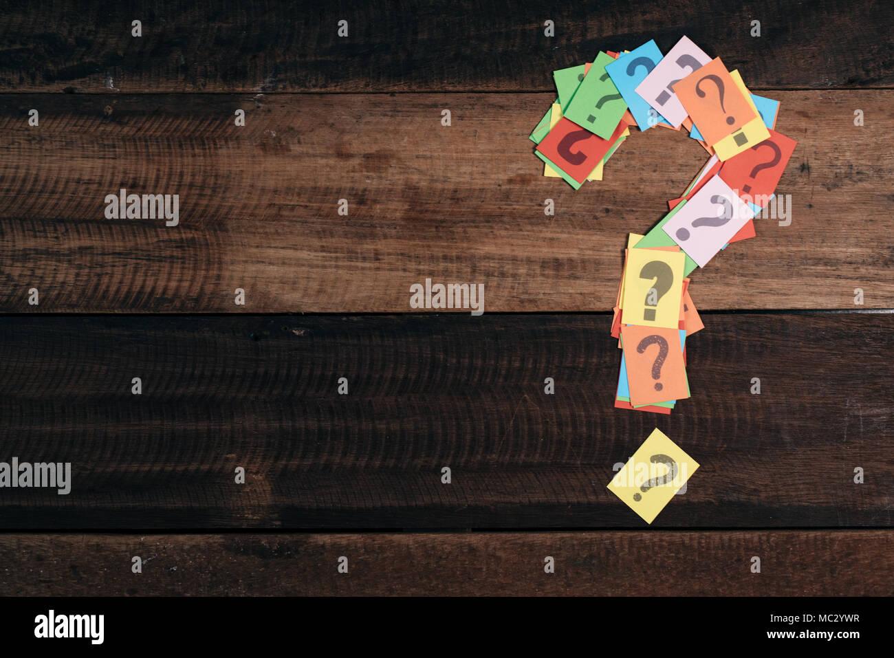 Papier multicolores avec point d'interrogation sur une table en bois fond. questions,mystère et concept de diversité. FAQ et Q&A concept d'arrière-plan Photo Stock