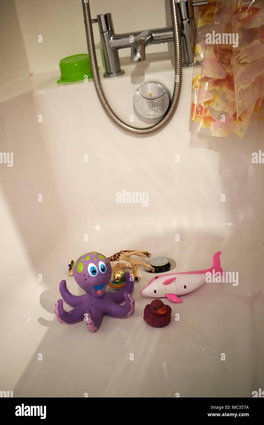 Les jouets d'enfant couché dans une baignoire vide Photo Stock