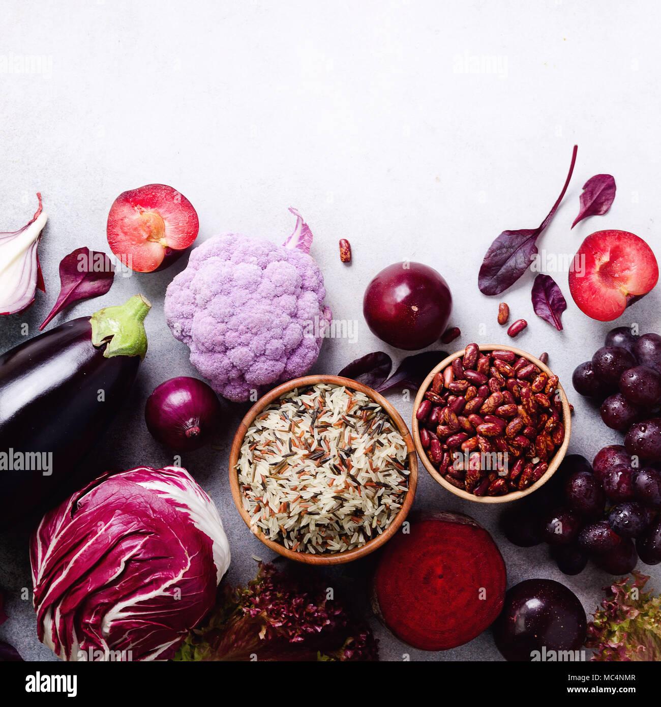Légumes, fruits violet sur fond gris. Violet aubergine, betterave, chou-fleur, haricots violets, les prunes, l'oignon, le chou, le raisin, le quinoa, le riz. Ingrédients pour la cuisine, l'espace de copie, vue du dessus, télévision lay Photo Stock