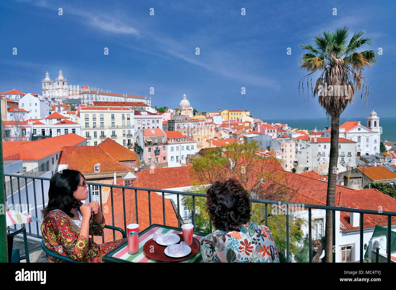 Deux femmes bénéficiant de boisson terrasse ensoleillée avec vue sur Lisbonne Photo Stock