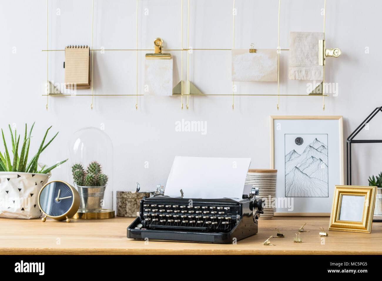 Un cadre doré organisateur sur un mur blanc au dessus dun bureau