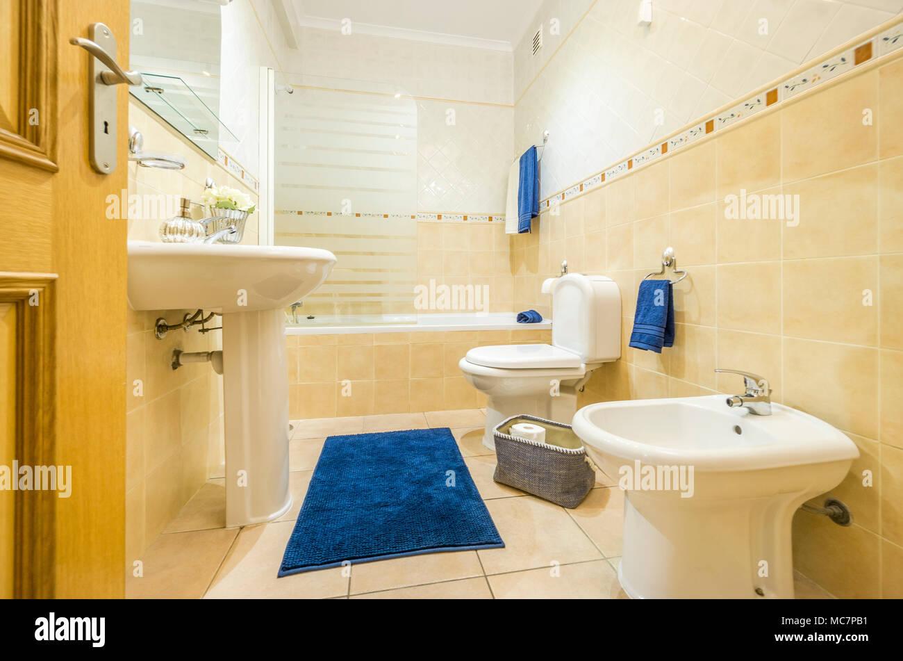 salle de bains classique dans des couleurs chaudes avec des serviettes et tapis bleu - Salle De Bain Classique