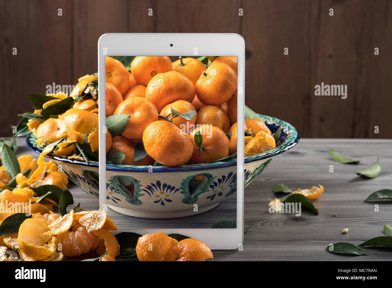 Tablettes mobiles blanc debout devant plat de céramique rempli de tangerines fraîches sur la table en bois gris. Pop up effet visuel. La composition des aliments créatif. Photo Stock