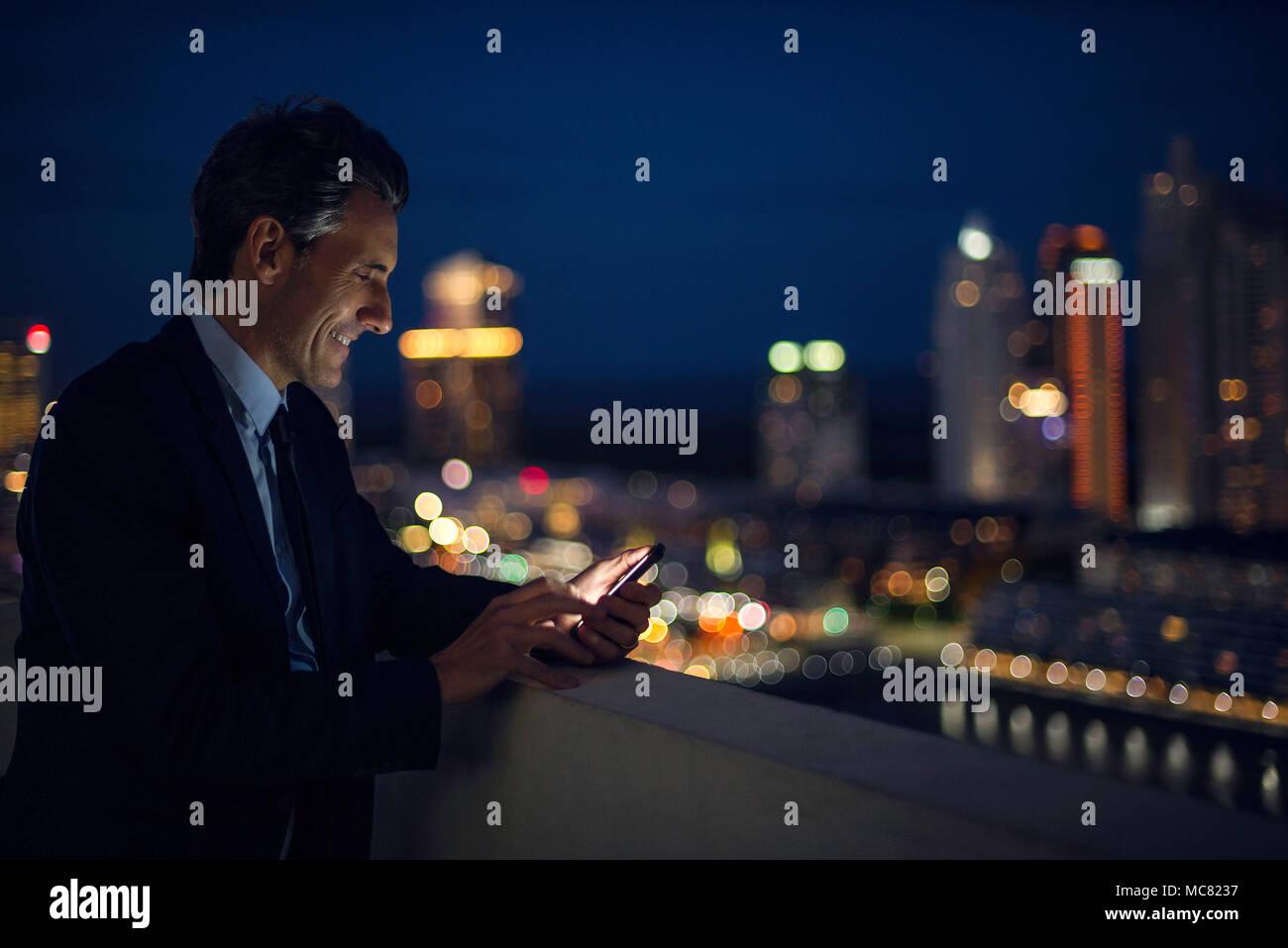 Homme d'affaires sur des tours à l'aide de téléphone mobile sur le toit Photo Stock