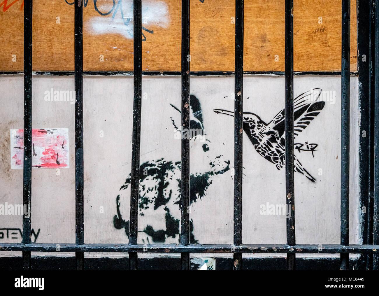 L'art de rue avec un lapin et oiseau de ronflement derrière les barreaux dans une ruelle étroite dans le centre de Bristol UK Photo Stock