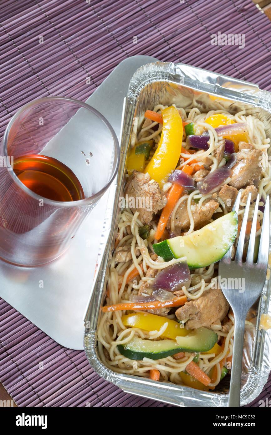 Chinois à emporter sauté de poulet et nouilles dans un plat de livraison d'aluminium avec un verre de Saki Photo Stock
