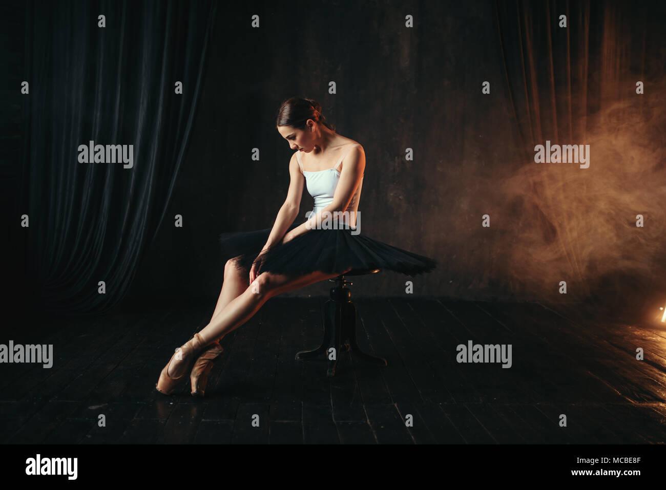 Ballerine assis sur banquette noir Photo Stock