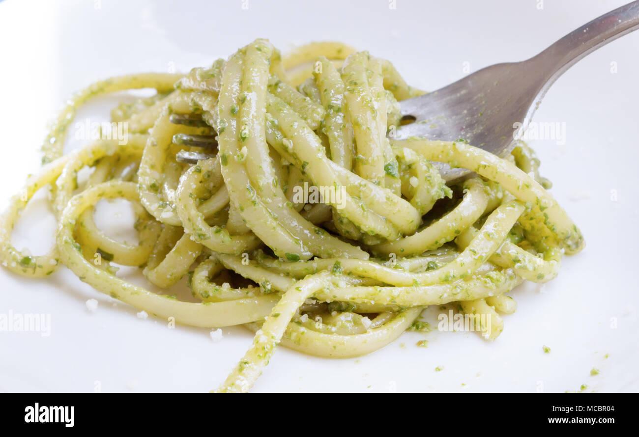 La nourriture italienne Spaghetti. Spaghetti avec sauce pesto fait maison et les feuilles de basilic sur la table avec la lumière du soleil, spaghetti avec sauce verte dans le Banque D'Images