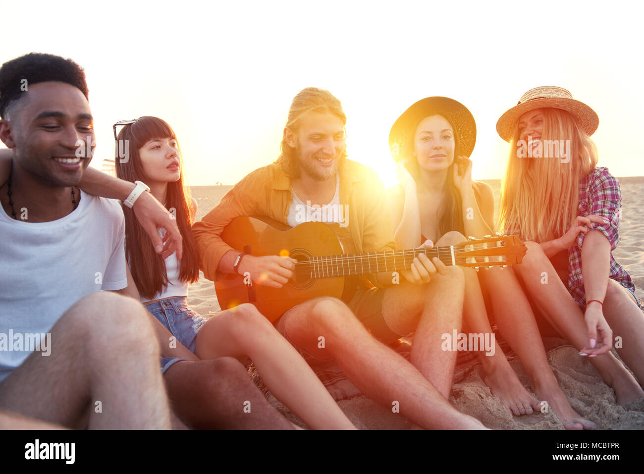 Joyeux groupe d'amis ayant fête sur la plage Photo Stock