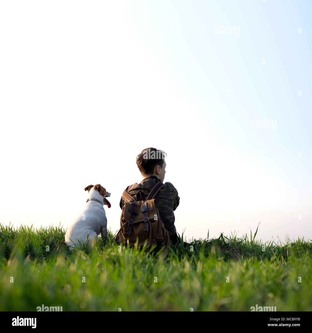 Adolescent sur pelouse verte avec petit chien blanc Photo Stock