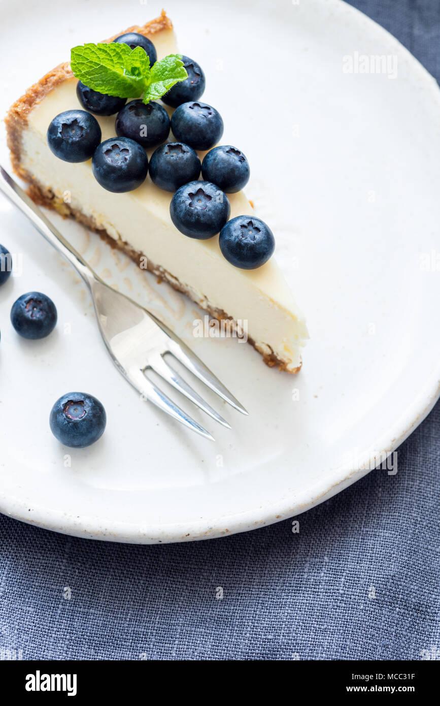 Morceau de gâteau au fromage avec des bleuets frais sur plaque blanche. Selective focus Banque D'Images