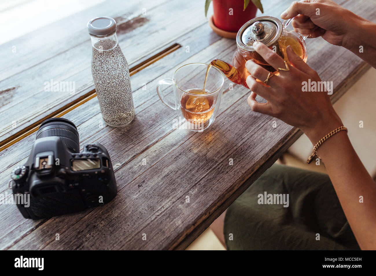 Close up of a woman pouring thé dans une tasse d'une théière en verre. La préparation du thé femme tandis qu'un appareil photo professionnel et une bouteille remplie de jus sont place Banque D'Images