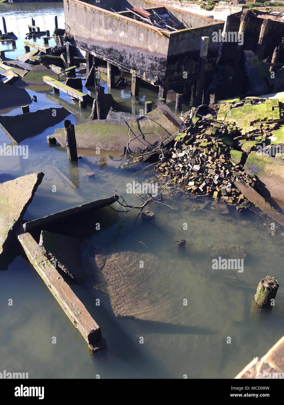 Nettoyage d'un déversement de pétrole dans le fleuve Columbia est en déclin, le 12 février 2018, après qu'un réservoir d'huile a été retiré de sous un pilier adjacent à la Cannery Pier Hotel & Spa, le 30 janvier 2018. Leur a pas eu plus d'huile car la suppression de la milieu des années 1900 réservoir d'huile, mais les restes d'huile restent sur des pilotis et jetée de rochers qui se dissipent naturellement et météorologiques. U.S. Coast Guard photo de Maître de 2e classe Mark Campanale. Photo Stock