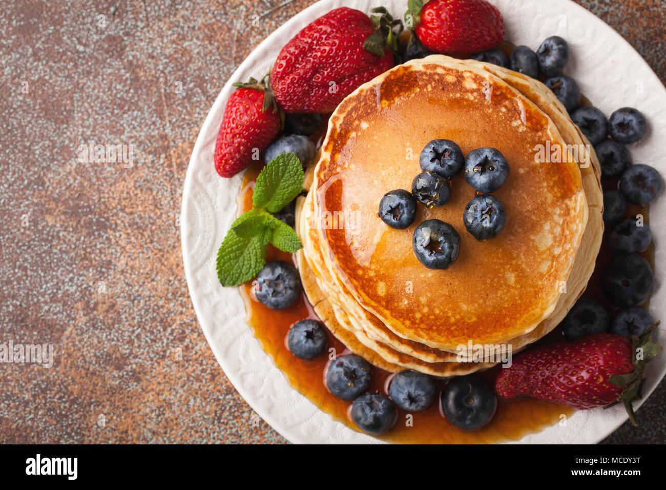 Close-up de délicieuses crêpes, avec des bleuets frais, fraises et sirop d'érable sur un arrière-plan rouillée. Avec l'exemplaire de l'espace. Vue d'en haut. Photo Stock