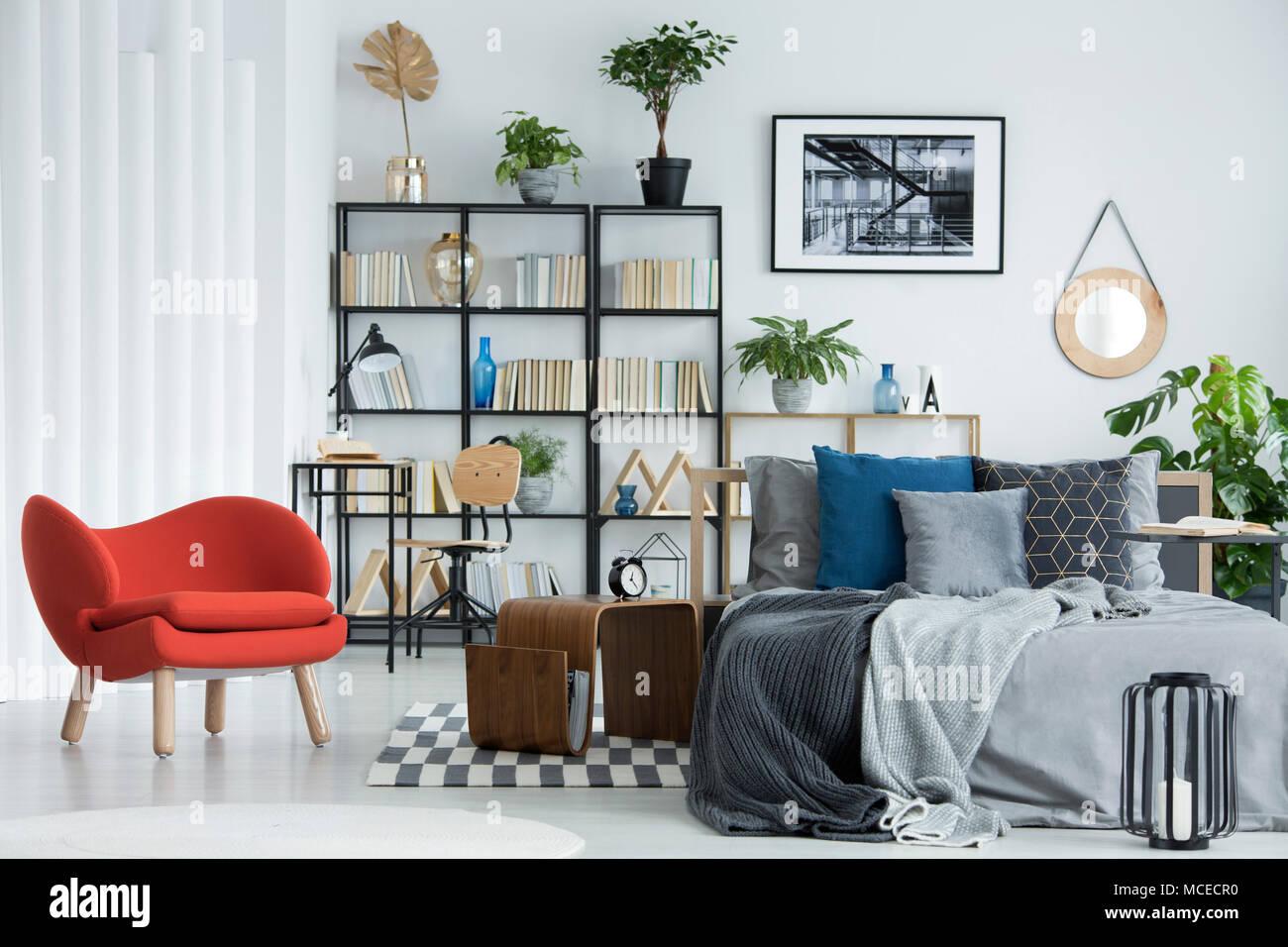 Fauteuil orange à côté de la table en bois et gris lit dans chambre ...