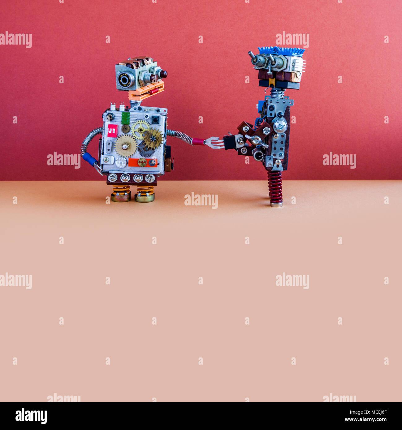 Deux robots saluent. Poignée de cyborgs mécanique cybernétique. Design créatif jouets robotisés, red wall brown marbre arrière-plan. Copy space Banque D'Images