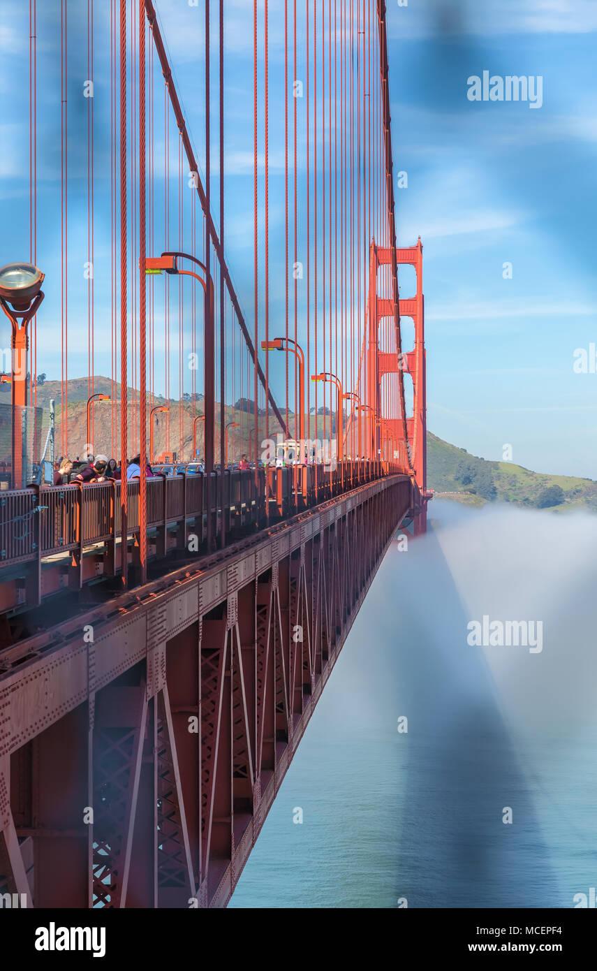 Vue sur le Golden Gate Bridge, avec le brouillard en dessous, à travers la barrière de sécurité, San Francisco, California, United States. Photo Stock
