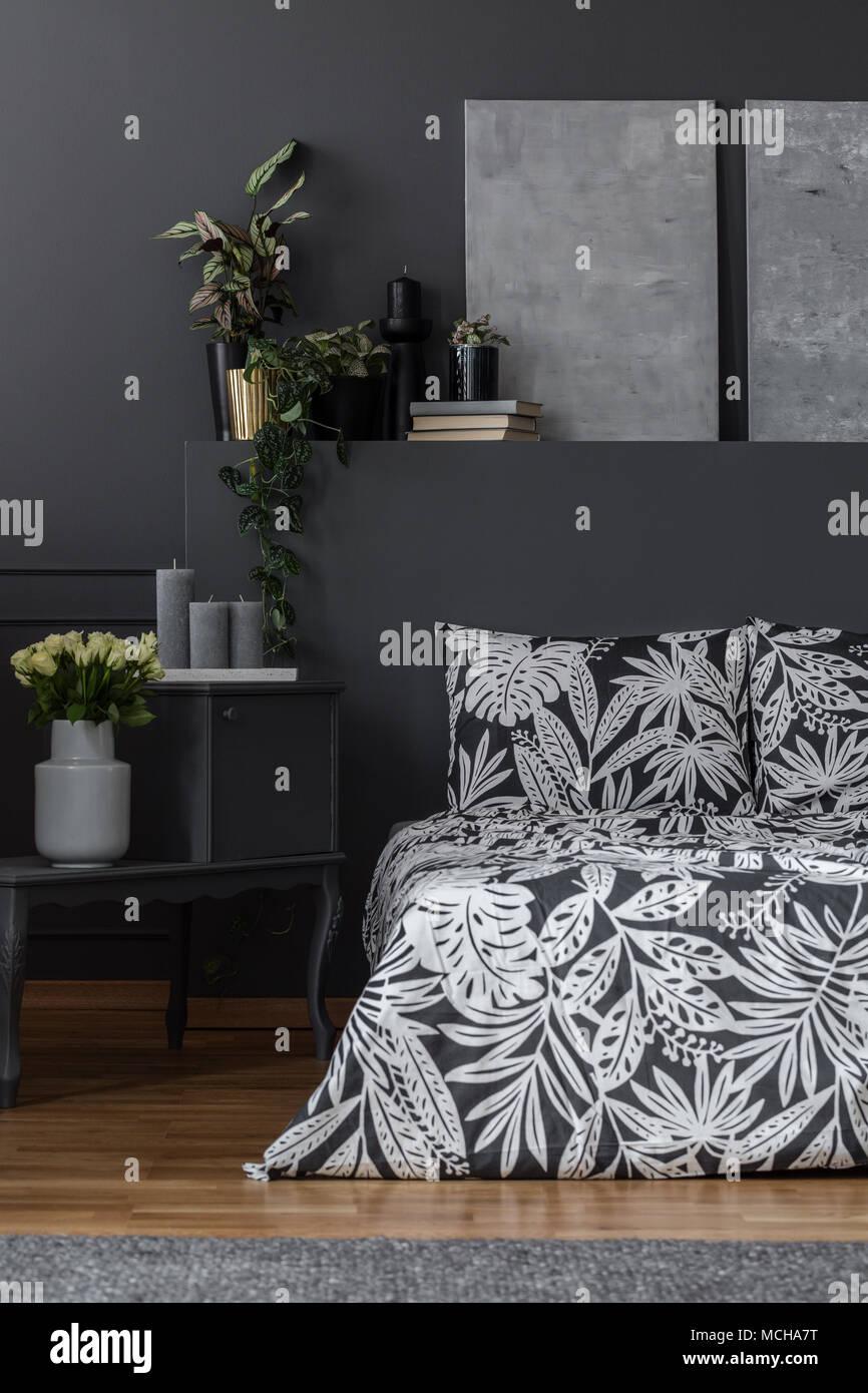 Peintures sur mur gris foncé au-dessus de lit à motifs dans le noir ...