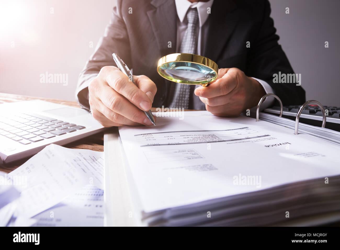 Close-up de la main de l'homme d'affaires à la loupe par les reçus au travail à Photo Stock