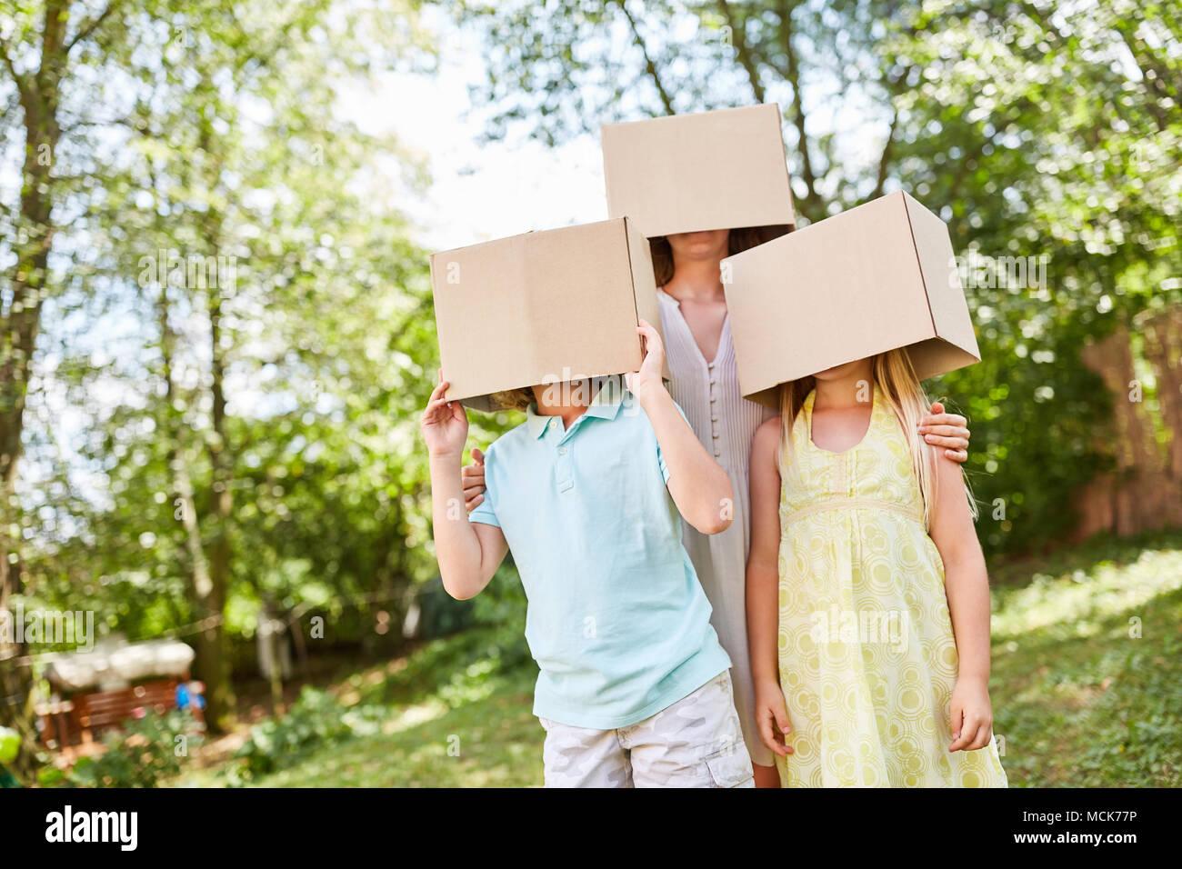 Les peuplements de la famille de façon anonyme avec les visages sous les boîtes de carton dans le jardin Photo Stock