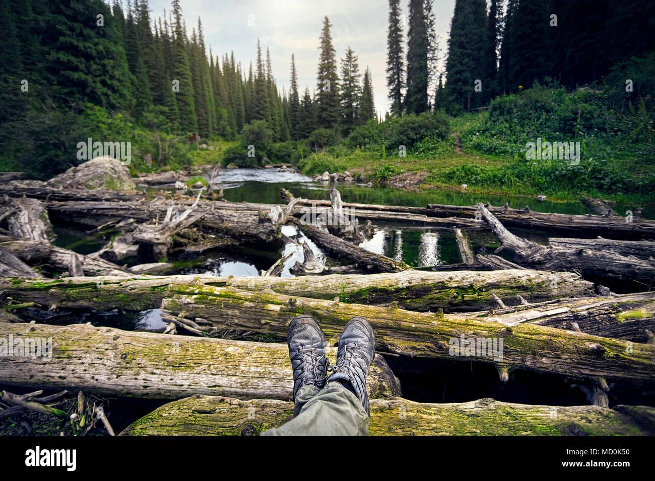 Les jambes de l'homme dans le suivi des chaussures et vue sur le bois et lac de montagne. Voyage en plein air concept. Photo Stock