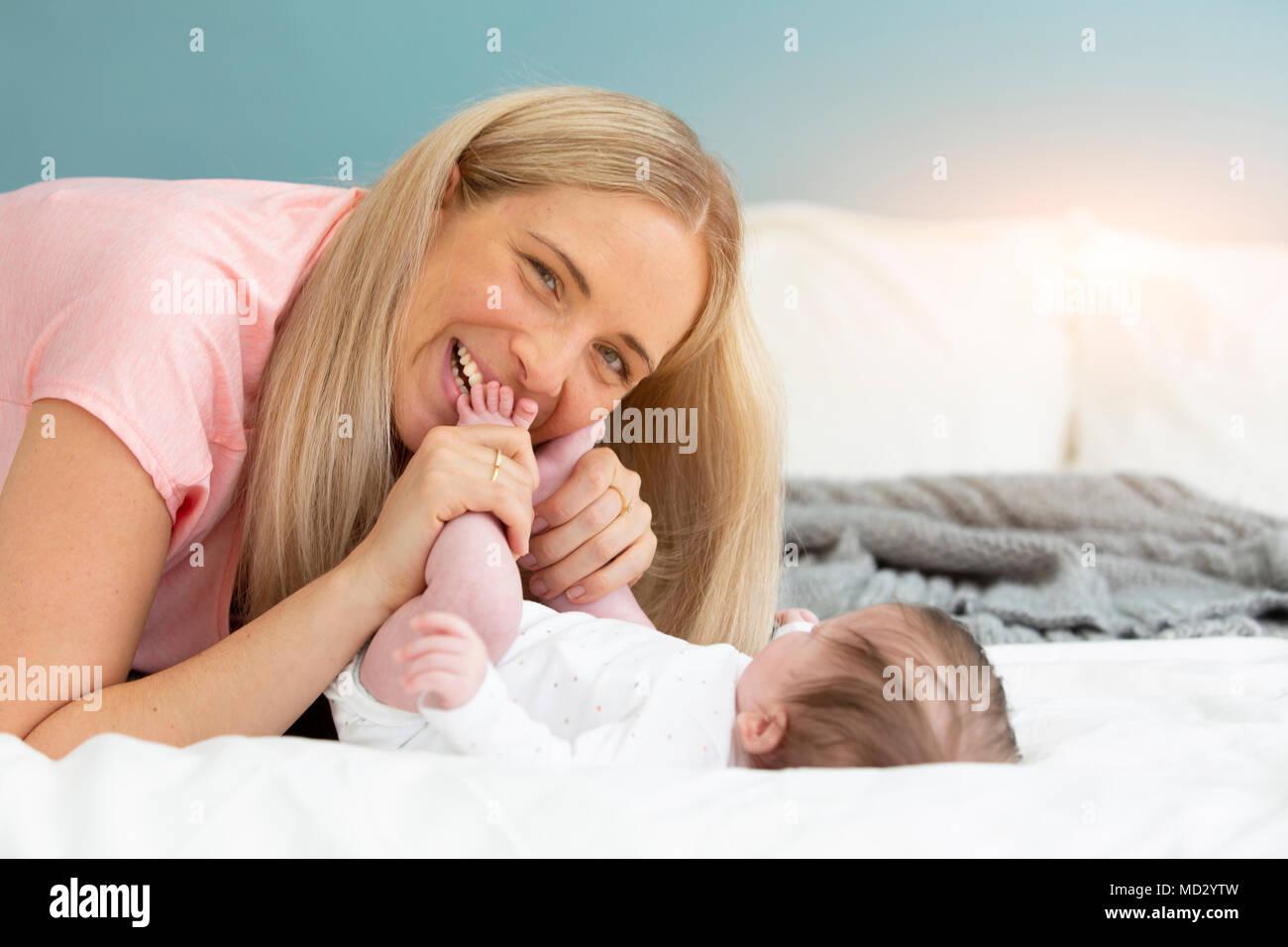 Jeune, belle et blonde mère avec chemise rose est de câlins avec son bébé au lit Photo Stock