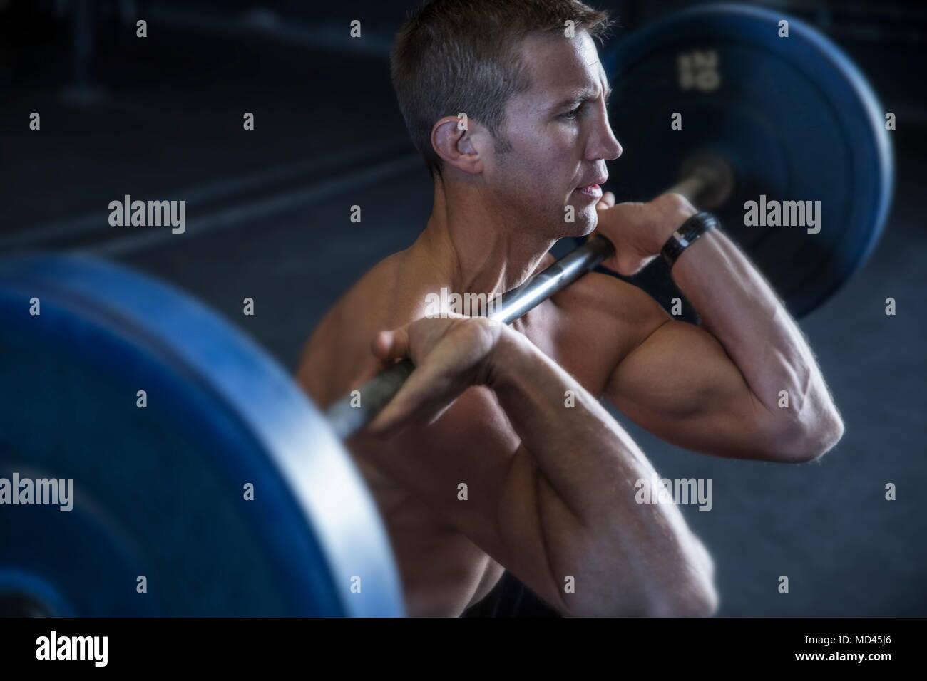 Dans l'exercice de l'homme de sport, à l'aide d'haltères longs avant, position accroupie Photo Stock