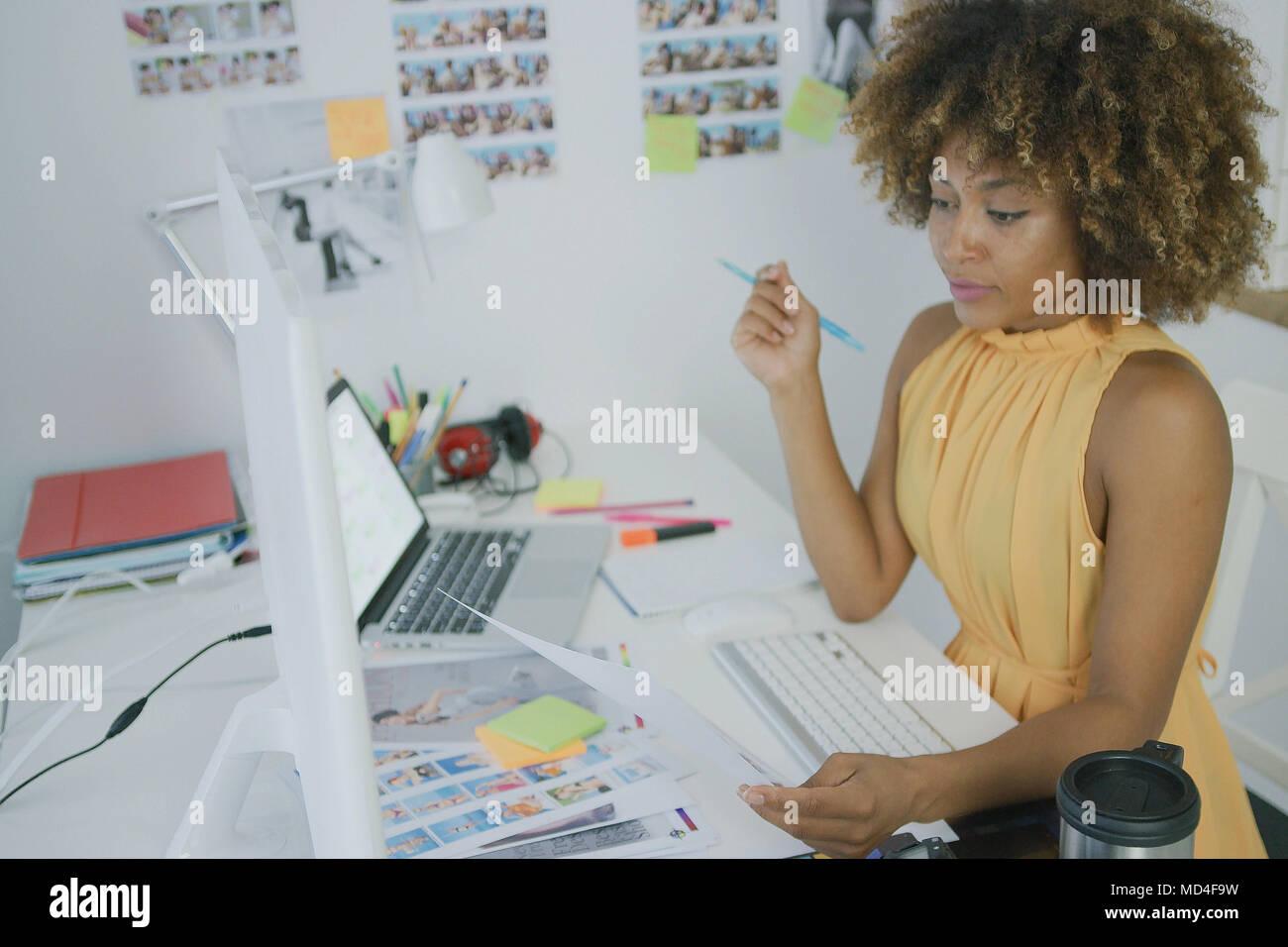 Designer élégant posing at desktop Photo Stock