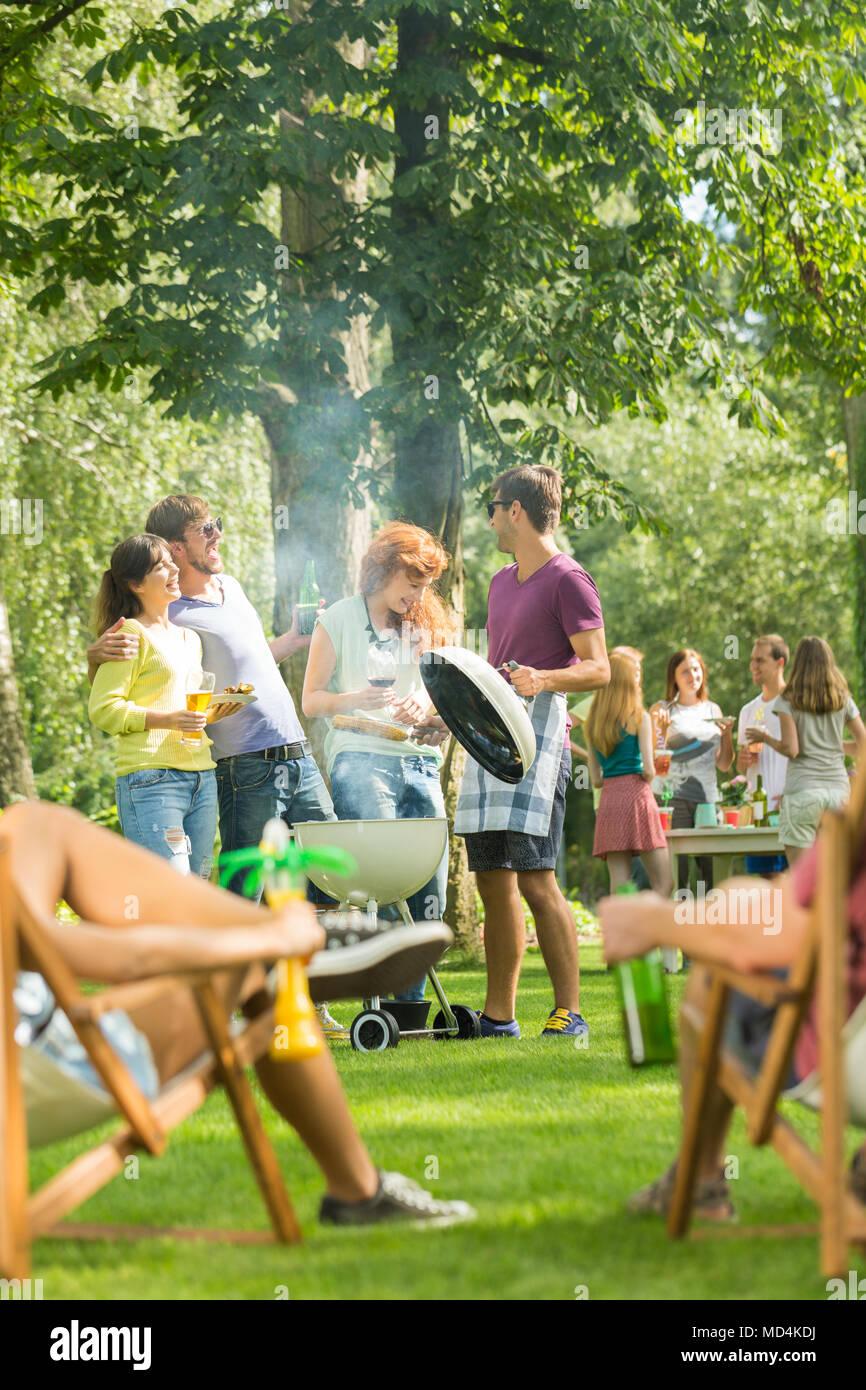Grill a tenu dans un parc par un grand groupe d'amis profitant du beau temps et de l'alimentation Banque D'Images
