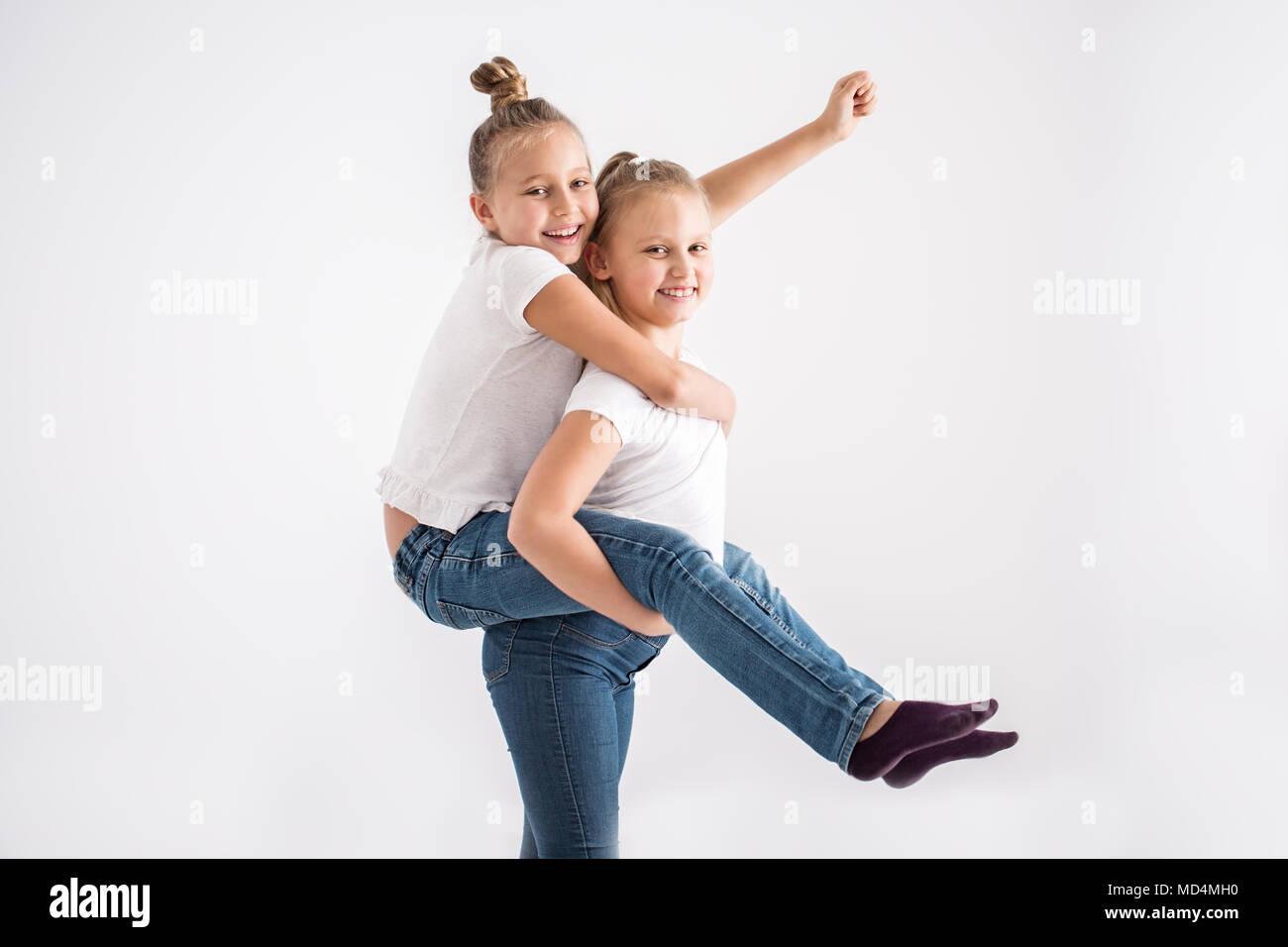 Portrait d'une jeune fille s'amusant, bénéficiant d'une piggyback ride sur sa sœur est de retour sur un fond blanc. Photo Stock