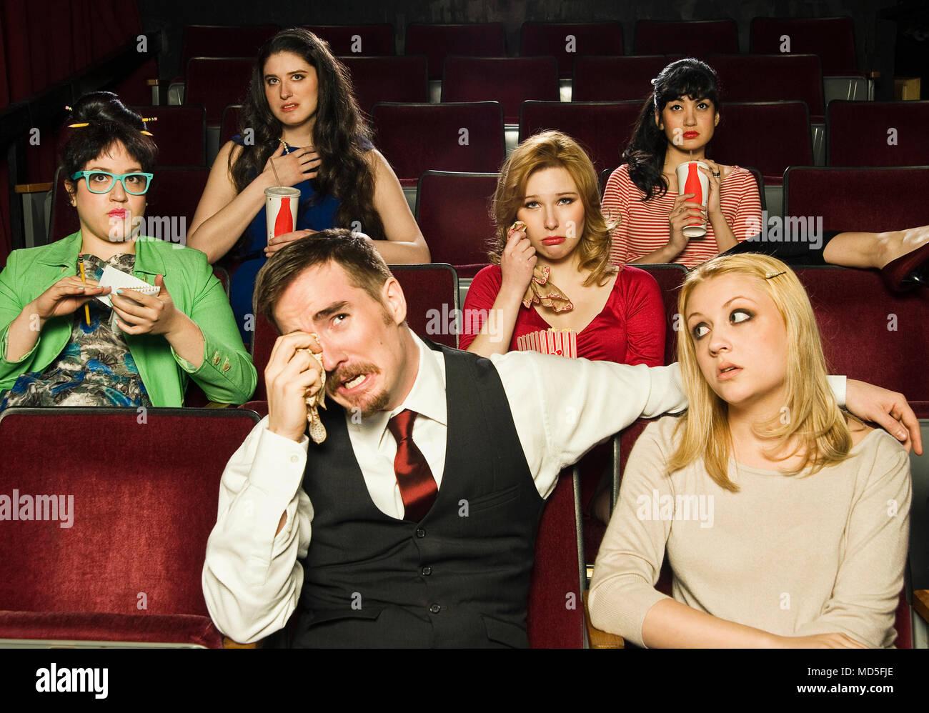 Un groupe de personnes réagissant à un film dans un cinéma. Photo Stock