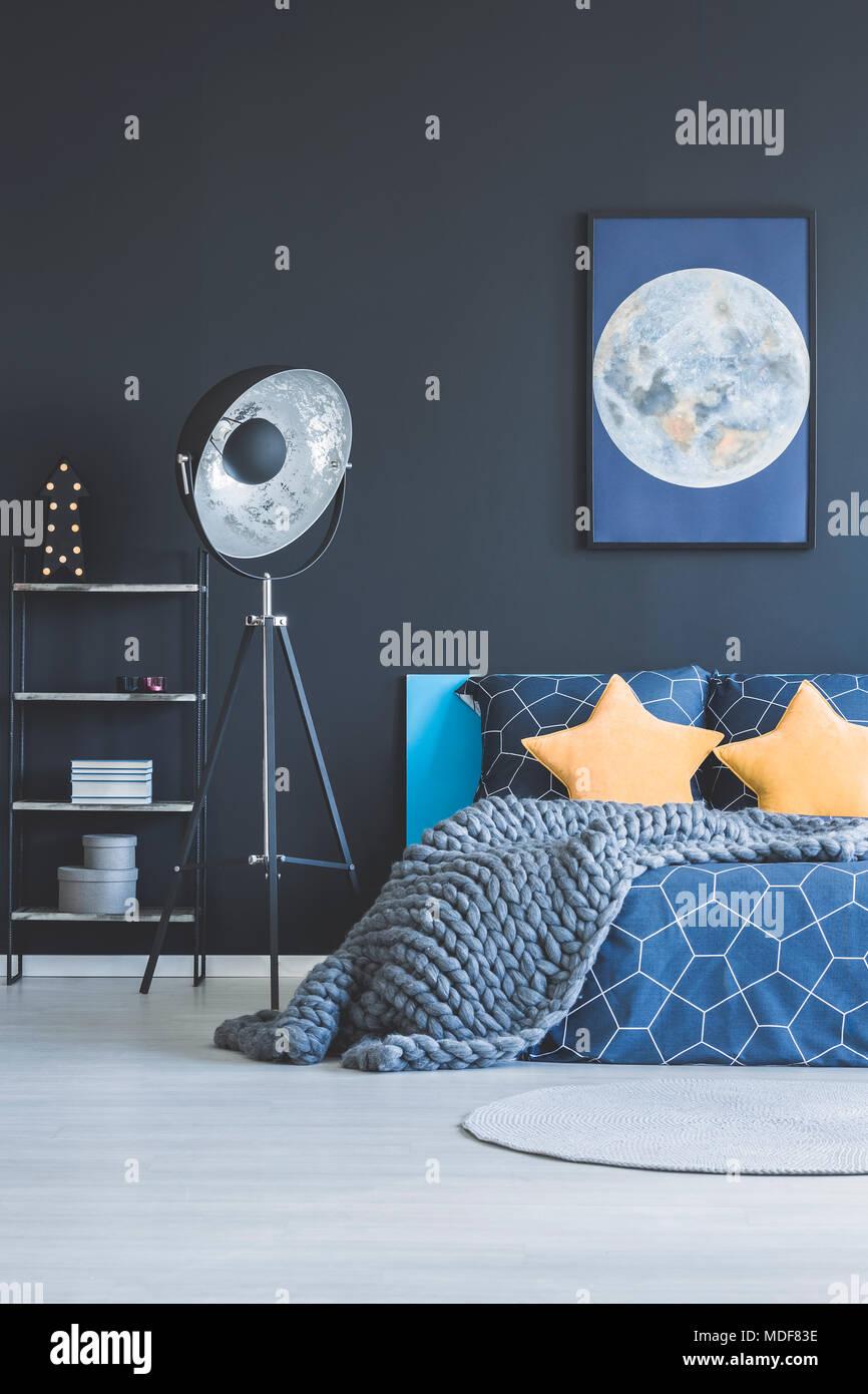 Étoile Jaune Les Oreillers Et Couverture Tricot Sur Lit Dans Chambre Bleu  Marine Intérieur Avec Lampe Industrielle