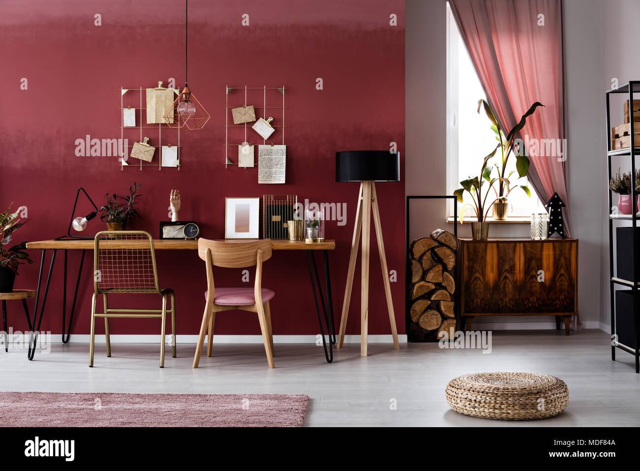 Plante sur armoire en bois contre une fenêtre en rouge foncé de l'intérieur de l'espace de travail avec fauteuil et pouf à une table Photo Stock